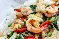 Fried basil shrimp with squid topped with rice stock photos