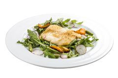 Fried bass with salad. On a white background royalty free stock photos
