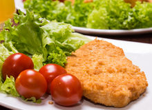 Fried battered chicken breast. Fillet  with lettuce on the plate Royalty Free Stock Image