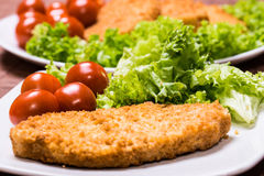 Fried battered chicken breast. Fillet  with lettuce on the plate Royalty Free Stock Images