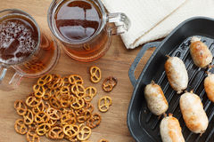 Fried bavarian sausages on the pan with beer and pretzel. Oktoberfest background Royalty Free Stock Photography
