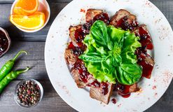 Fried beef meat with wild berries sauce on plate on wooden background. royalty free stock photos
