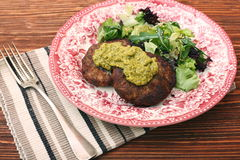 Fried beef patties with pesto sauce and greens Royalty Free Stock Photography
