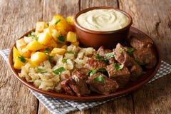 Fried Beef Rydberg tjänade som med lökar och knapriga potatisar med närbild för senapsgult sås på tabellen horisontal royaltyfri bild