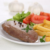 Fried beef steak meat meal with fries, vegetables and lettuce on Stock Photos