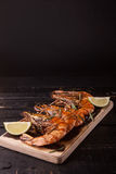 Fried big tiger shrimp on the wooden cutting board. With lime Stock Photography