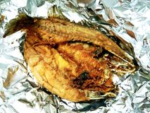 Fried black-banded trevally in tin foil. Fried black-banded trevally wrapped and served in tin foil Royalty Free Stock Photography