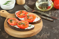 Fried black bread with cheese, tomatoes and greens for lunch. Sandwich with soft cheese and tomatoes on dark bread Royalty Free Stock Images