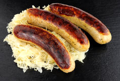 Fried Bratwurst Sausages And Sauerkraut Stock Photos