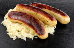 Fried Bratwurst Sausages And Sauerkraut Stock Photography