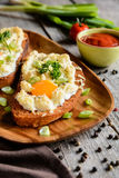 Fried bread with eggs, cheese and onion Stock Photo