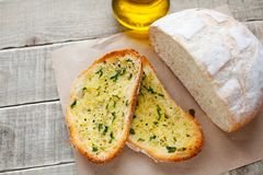 Fried bread with olive oil, garlic and herbs on a wooden table. Rustic style Royalty Free Stock Image