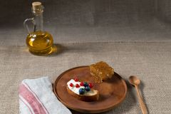 Fried bread, toast with yoghurt and berries, bilberries, blueberries and red currants on a wooden plate with honey combs and bottl Royalty Free Stock Photos