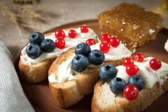 Fried bread, toast with yoghurt and berries, bilberries, blueberries and red currants on a wooden plate with honey honeycomb Stock Photography