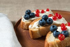 Fried bread, toast with yoghurt and berries, bilberries, blueberries and red currants on a wooden plate o Stock Photos