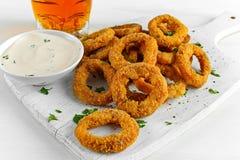 Fried Breaded Onion Rings mit Soße und hellem Bier auf weißem hölzernem Brett, Hintergrund lizenzfreies stockbild