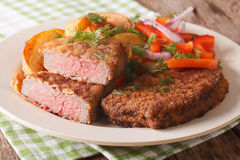 Fried Breaded rump steak with potato and vegetables close-up. ho. Fried Breaded rump steak with potato and vegetables close-up on a plate. horizontal Royalty Free Stock Photography