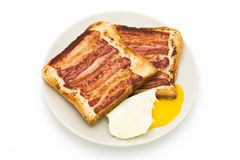Fried breakfast. Delicious fried breakfast with toast, bacon and egg on a white plate Stock Photography