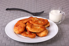 Fried cakes on white plate, fork and cup of milk Stock Image