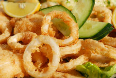 Fried Calamari. With arugula salad, lemon, and vegetables royalty free stock images