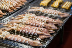 Fried calamari bbq on stick is sold at the Asian street  market Stock Photo