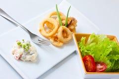 Fried Calamari. And lettuce leaf on white tray Royalty Free Stock Photos