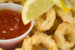 Fried Calamari med Marinara sås och citroncloseupen Arkivfoton
