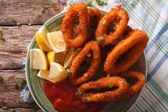 Fried calamari rings close up with ketchup and lemon. Horizontal Royalty Free Stock Image