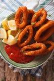 Fried calamari rings close up with ketchup and lemon. Vertical t Royalty Free Stock Image