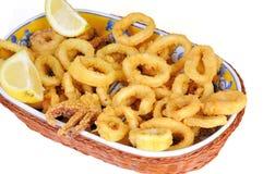 Fried calamari rings dipped in batter with lemon Stock Image