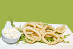 Fried calamari rings served tartar sauce and rocket salad leaves Royalty Free Stock Images