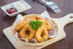 Fried calamari rings in wicker basket and sauce Stock Image