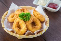 Fried calamari rings in wicker basket and sauce Royalty Free Stock Photo