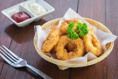Fried calamari rings in wicker basket and sauce. Fried calamari rings in a wicker basket and sauce Stock Image
