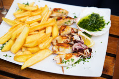 Fried calamari served with fries at a restaurant Royalty Free Stock Images