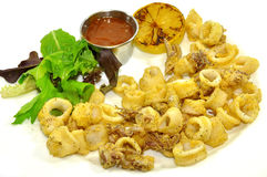Fried calamari. Served with sauce, lemon, and spinach Royalty Free Stock Photography