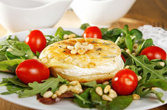Fried camembert. Served with green salad, cherry tomatoes and pine nuts Stock Photos