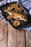 Fried carp with lemon, onion and spices on the grill pan Stock Images