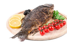 Fried carp on wooden platter. Royalty Free Stock Images