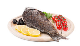 Fried carp on wooden platter. Royalty Free Stock Photography