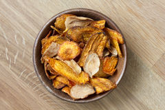 Fried carrot and parsnip chips in rustic wood bowl. From above. Stock Photos