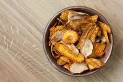 Fried carrot and parsnip chips in rustic wood bowl. From above. Stock Photography
