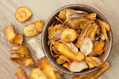 Fried carrot and parsnip chips in rustic wood bowl. From above. Royalty Free Stock Image