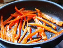 Fried carrots. Closeup slices of carrots frying in a pan Royalty Free Stock Images