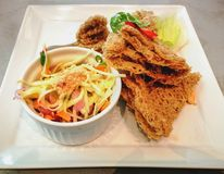 Fried catfish skin with Som Tum or green papaya salad on the whi. Te dish. Thai food Stock Images