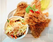 Fried catfish skin with Som Tum or green papaya salad on the whi. Te dish. Thai food stock image