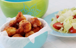 Fried cauliflower with fresh vegetable salad. Fried cauliflower served on blue bowl. Vegetable salad with tomatoes and lettuce on background Stock Photo