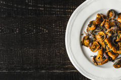 Fried chanterelles in the ceramic plate  at the right of the old wooden table top view Royalty Free Stock Photos