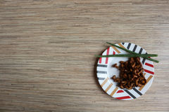 Fried chanterelles on the plate. With green onion on bamboo background Stock Photos
