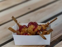 Fried cheese balls in a box on a wooden table royalty free stock photos
